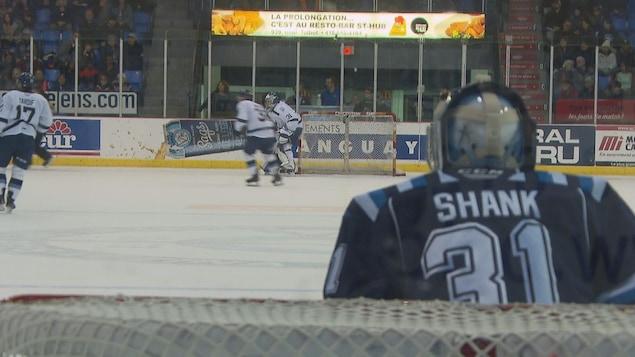 Le gardien de but Alexis Shank suit des yeux l'action qui se déroule à l'autre bout de la patinoire.