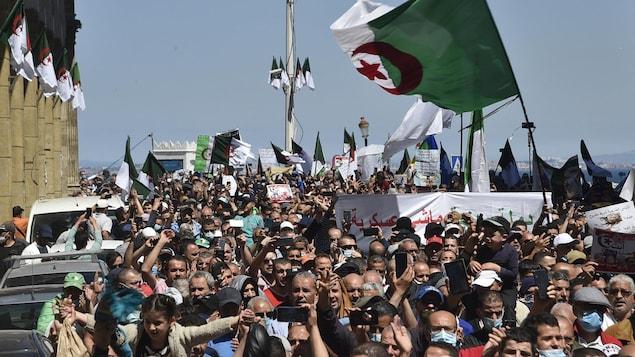Une foule de manifestants portant des drapeaux et des banderoles.