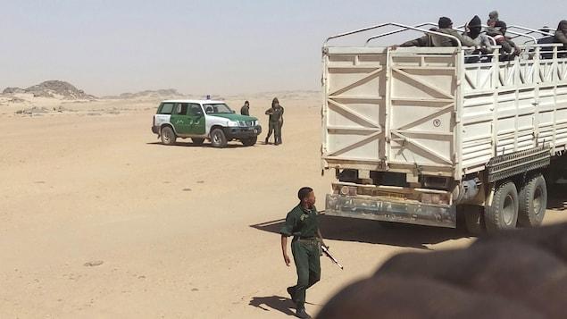 Une photo fournie par Ju Dennis, un migrant libérien, qui montre des gendarmes algériens armés chargeant des migrants sur des camions pour les déposer à la frontière nigérienne.