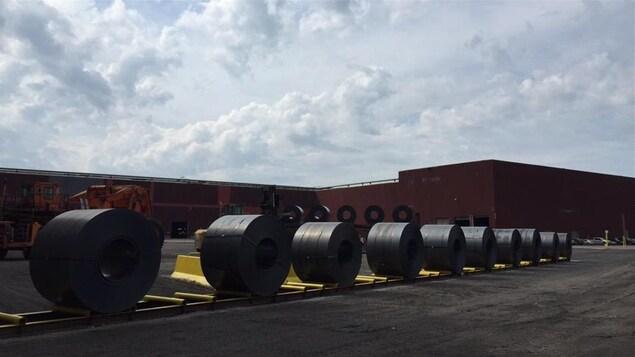 Bobine d'acier devant une usine.
