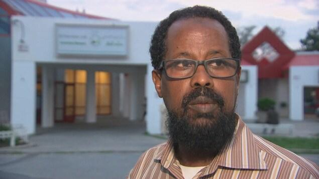 Un homme devant un bâtiment.