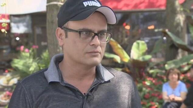 Un homme avec des lunettes et une casquette.