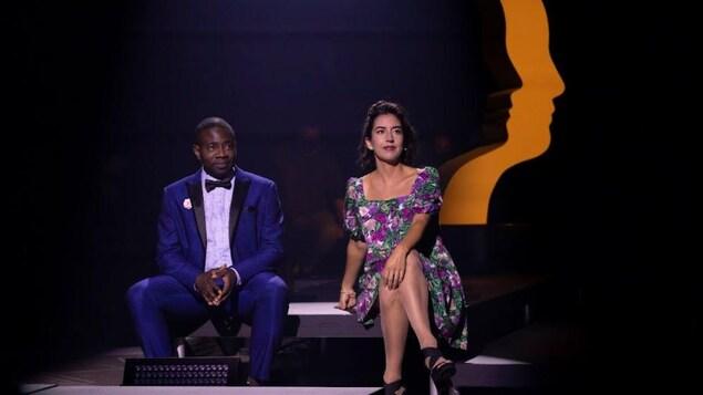 Un homme et une femme assis sur scène, devant une statuette géante d'un prix gémeaux