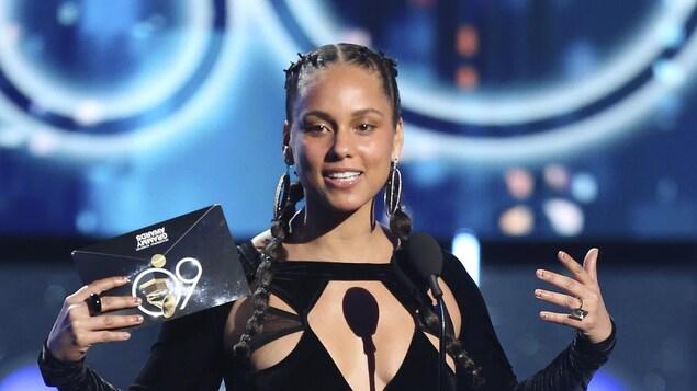 Alicia Keys s'exprimant sur une scène. Elle porte une robe noire et a une enveloppe des Grammy Awards dans sa main droite.