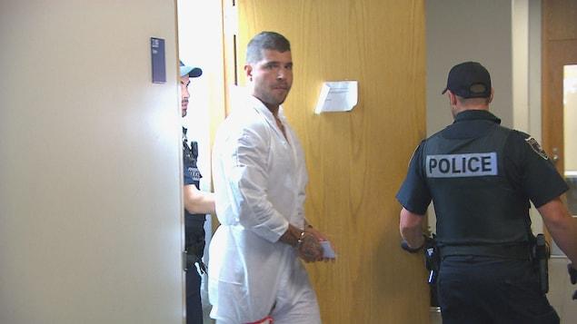 Un homme en combinaison de prisonnier est menotté et sors d'une pièce.