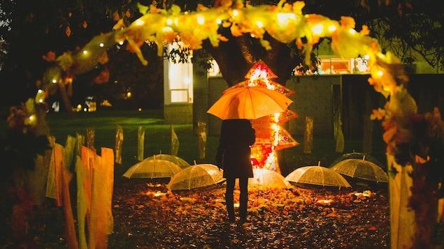 Une femme se tient devant un sanctuaire pour honorer les personnes décédés au cours de la dernière année.