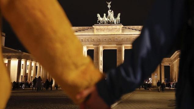 Deux personnes se tiennent la main devant la porte de Brandebourg à Berlin, le soir.