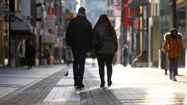 Un couple, vu de dos, marche dans une rue désertée d'un centre-ville.