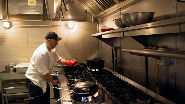 Photo d'un cuisinier devant son poêle.