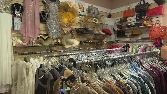 Des vêtements sont pendus à des cintres, et des chapeaux, foulard, sacs et autres articles sont en montre sur des présentoirs, dans un coin de la boutique.