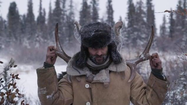 Un homme dans une région nordique tenant sur ses épaules le panache d'un orignal.
