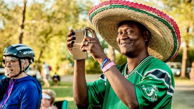 Alpha Barry portant un sombréro et un chandail des Roughriders prend une photo à l'aide de son téléphone intelligent.