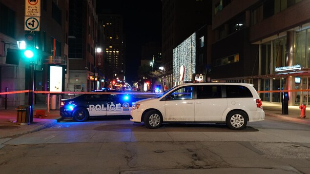 Une voiture de police bloque la rue. Un cordon de sécurité a été installé.