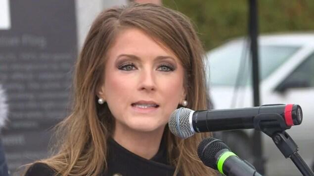 Une femme devant des micros.