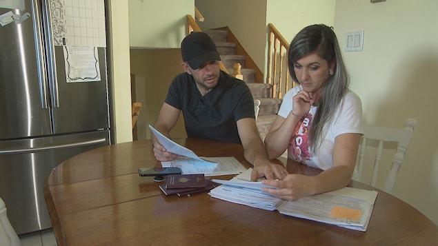 Alexandre et Amandine Moyroud regardent des documents officiels.