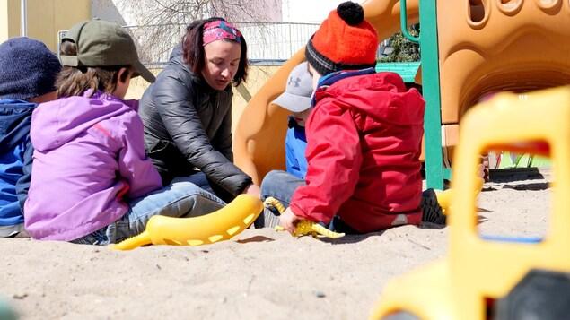 De jeunes enfants jouent dans le sable avec Amandine Falette-Galiussi.