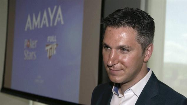 David Baazov photographié à côté d'un écran où l'on voit le nom Amaya.