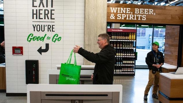 Un homme dans un supermarché tient un sac d'épicerie vert sur lequel est écrit « Amazon go grocery ».