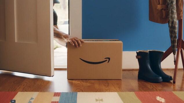 Un livreur entrouvre la porte d'un client pour déposer un colis à l'intérieur de la maison.