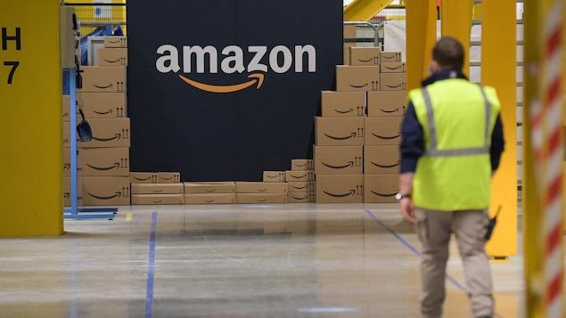Un employé marche vers un mur affichant le logo d'Amazon.