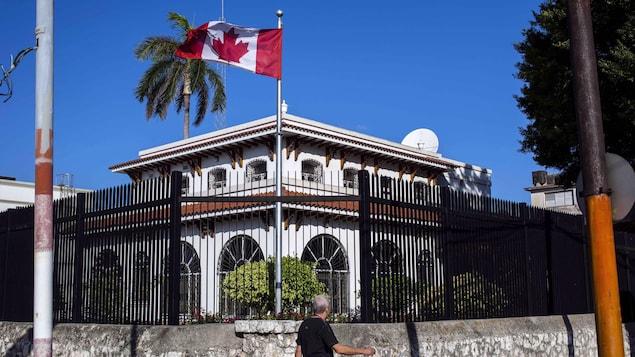 Un drapeau canadien flotte devant l'édifice clôturé de l'ambassade canadienne à Cuba.