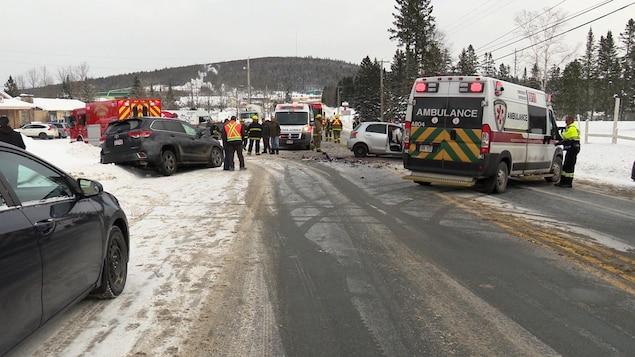 Scène d'accident sur une route enneigée avec plusieurs badeaux, des pompiers et deux ambulances.