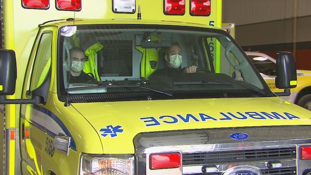 Des ambulanciers portent un masque dans leur véhicule.