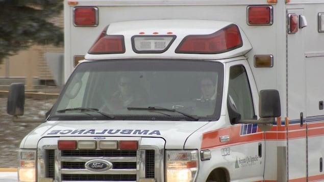 Une ambulance aux phares allumés avec deux personnes assises devant.
