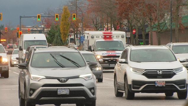 Des voitures et une ambulance sur un boulevard.