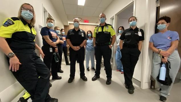 Une dizaine d'employés de la santé debout dans un hôpital.