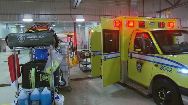 Du matériel médical s'apprête à être transféré à bord d'une ambulance qui est stationnée à l'intérieur d'un garage.