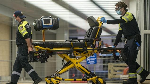 Deux ambulanciers poussent une civière après avoir transporté un patient à l'hôpital.