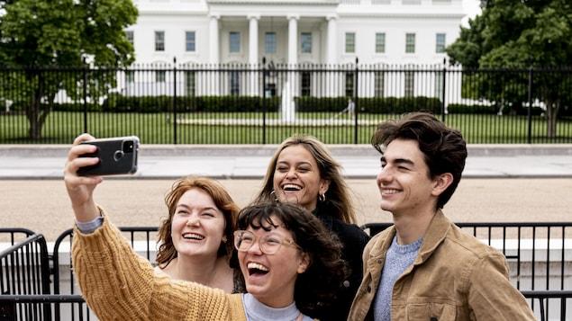 Tout sourire, quatre jeunes dans le parc Lafayette, où subsistent des barrières, se photographient devant la Maison-Blanche.