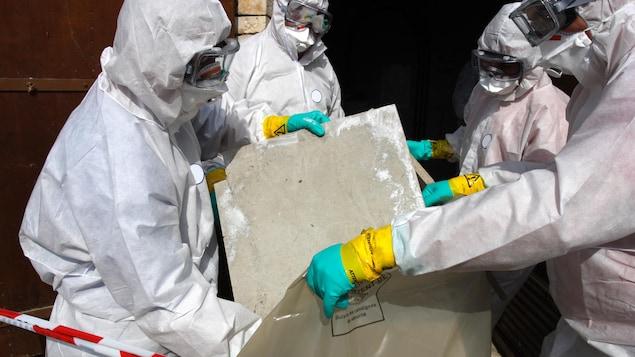 Des travailleurs en combinaison manipulent de l'amiante.