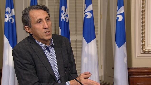 Amir Khadir, député de Québec solidaire dans Mercier, en point de presse à l'Assemblée nationale, avec des drapeaux du Québec derrière lui.