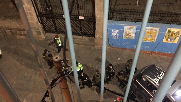 La vue d'un balcon montre des policiers stationnés dans la rue devant une auberge.