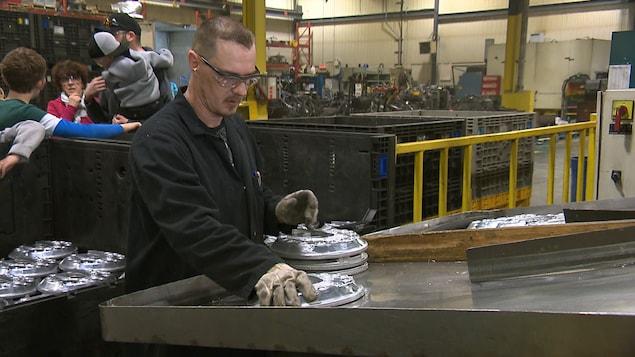 Un employé de l'entreprise AMT Moulage récupère des pièces produite pour des constructeurs automobiles.