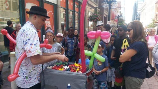 Un homme transforme des ballons en animaux pour les enfants.