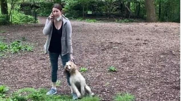 Amy Cooper parle au téléphone en tenant son chien par le collier.