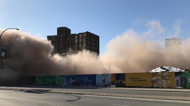 Un nuage de fumée s'élève de la base du bâtiment.