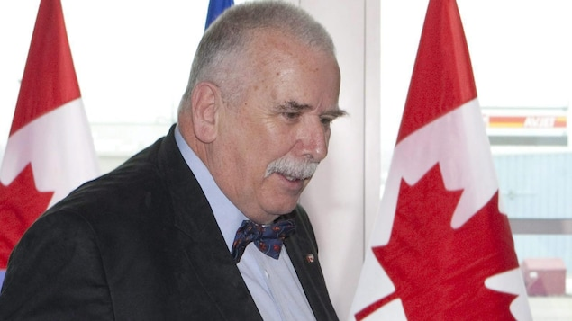 André Arthur, vu de profil, sur fond de drapeaux du Canada.