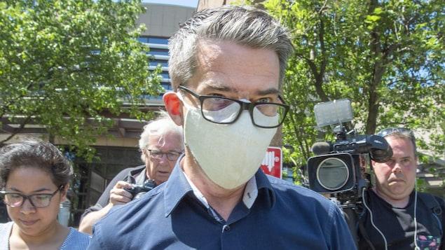 Portant un masque, M. Boisclair regarde au loin.