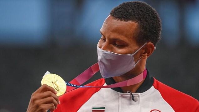 Andre De Grasse, le visage masqué, regarde sa médaille d'or.