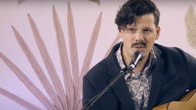 L'auteur-compositeur-interprète André Péloquin-Hopfner devant un micro avec sa guitare