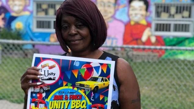 Andrea Tabnor tient une pancarte du barbecue Unity très colorée entre ses mains, elle a les cheveux noirs-aburn