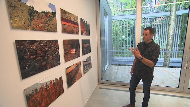 Un homme montrant des photos de forêts brulées accrochées sur un mur.