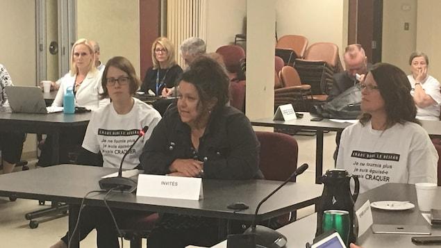 Trois représentantes syndicales assises à une table dans une réunion d'un conseil d'administration
