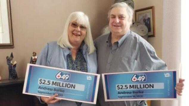 Andrew Burke et sa femme tenant chacun un chèque de 2,5 millions de dollars.