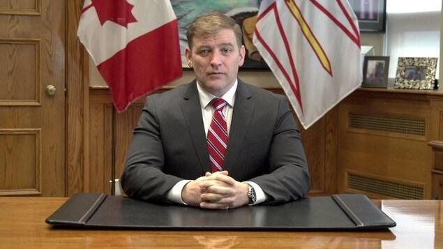 Andrew Furey assis les mains croisées à un bureau brun. Un drapeau de Terre-Neuve-et-Labrador et un drapeau du Canada sont derrière lui.
