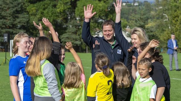 Andrew Scheer, sa femme et des enfants ont une main en l'air, comme s'ils faisaient un cri d'équipe.